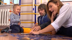 Young caucasian family assembling puzzle and reading book together. Man, woman Stock Footage