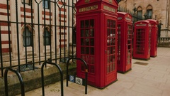 Tilting shot of the Royal Courts of Justice with three red phone booths Stock Footage
