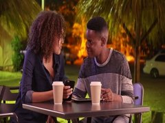 Young African American couple have coffee at night in a small town Stock Footage