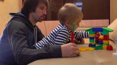 Father and his little son playing with colorful construction set together Stock Footage