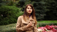 Portrait of a young beautiful woman in beige coat posing on a background of autu Stock Footage
