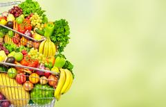 Vegetables and fruits over green background. Stock Photos