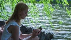 Beautiful Girl Using SmartPhone Sitting Near Lake in City Park Stock Footage