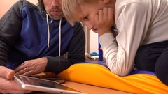Father and his little son watching movie on tablet PC together. Parental control Stock Footage