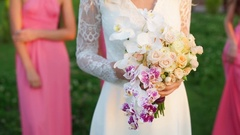 Bride with bouquet of orchids and roses in hand, girlfriend in the background Stock Footage