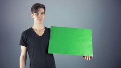 Young man in black shirt holding green key sheet poster gray background Stock Footage