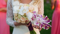 The bride touches with his hands a bouquet of roses and orchids, bridesmaids Stock Footage