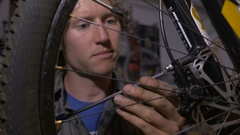 A young bicycle mechanic working on a mountain bike - dolly shot Stock Footage