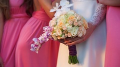 Bride with bouquet of orchids and roses in hand, surrounded by bridesmaids Stock Footage