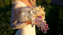 The bride touches with his hands a bouquet of roses and orchids in the bright Stock Footage
