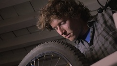 Low angle of a millennial man bike mechanic working on a bicycle wheel Stock Footage
