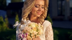 Gentle happy bride standing with a bouquet of roses and orchids in the bright Stock Footage