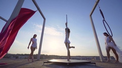 Three beautiful sexy girl performing acrobatic stunts on the roof with a nice Stock Footage