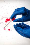 Forensic technician taking DNA sample from blood stain Stock Photos