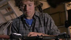 A young bike mechanic works at the front end of a bicycle Stock Footage
