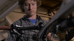 A millennial man bike mechanic adjusting cables and shifters on bike Stock Footage