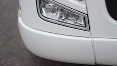 Front view of a truck headlight closeup in rainy weather, camera paning Stock Footage