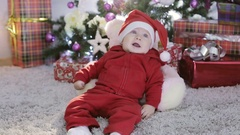 Baby boy in Santa costume sitting under the Christmas tree and falls. Stock Footage