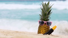 Pineapple fruit in sunglasses and sunscreen protection cream bottle on beach Stock Footage