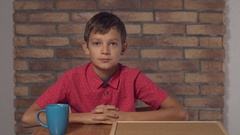 Child sitting at the desk holding flipchart with lettering coffee on the Stock Footage