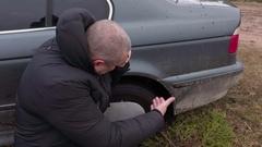 Man talking on phone near  stuck car  in the mud Stock Footage