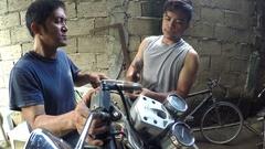 Motor bike repairmen hammering metal handle Stock Footage