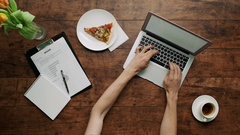 Man's arms typing on laptop Wooden table pizza slice aside cup of coffee office Stock Footage
