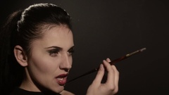 Beautiful woman smokes a cigarette in a mouthpiece on a black background Stock Footage