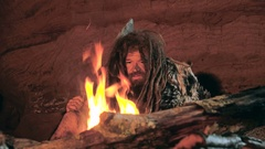Prehistoric caveman looks at the fire and his spear in his cave Stock Footage