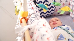 Little baby lying in his bed, looking at toys Stock Footage