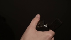 Woman's hand ignites vintage cigarette lighter on a black background Stock Footage