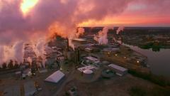 Many smokestacks billowing smoke into red predawn sky Stock Footage
