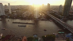 Flying over Bangkok Chaopraya river at sunset facing Thonburi Stock Footage