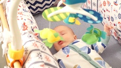 Close up, the child lies in bed and playing with toys, slidecam Stock Footage