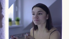 Beautiful woman dyes her eyelashes in bathroom Stock Footage