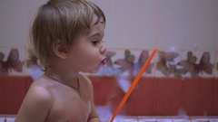 Child fun blowing soap bubbles in the bathtub Stock Footage