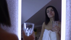 Beautiful brunette wearing a towel drinking a glass of water Stock Footage
