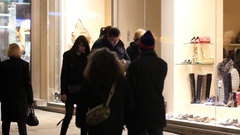 Shopping people watch glass store showcase in evening city center of Vienna Stock Footage