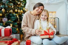 Cute girl and her grandma with xmas gifts looking at camera Stock Photos