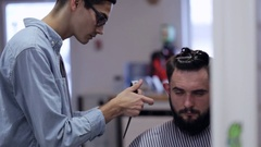 Handsome man with beard in barbershop. Barber working with electric razor. Stock Footage