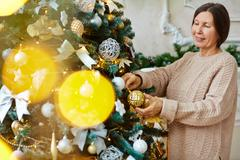 Happy senior female decorating Christmas tree at home Stock Photos