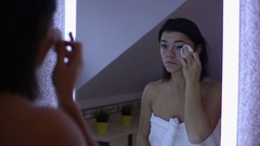 Young woman  cleaning her eyes with cotton pad in bathroom Stock Footage