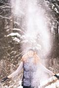 Winter fun in old wood. Girl in winter clothes throwing snow up in air Stock Photos