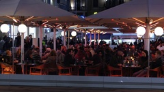People crowd eating food and drink sit at street restaurant tables in Vienna Stock Footage