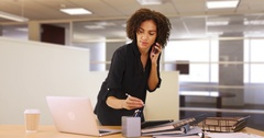 Businesswoman using laptop computer in office, listening on smartphone device. Stock Footage