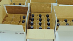 Packaging bottle with alcohol. Work puts bottle of wine in cardboard boxes Stock Footage