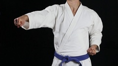 The fighter in white kimono with a blue belt making punch Stock Footage