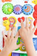 Child hands playing with educational toy Stock Photos