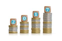 2017 Year money or financial growth concept with pile of coins and wooden cubes Stock Photos