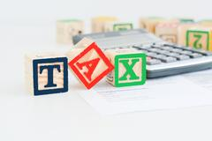 Taxation concept with wooden cubes and pocket calculator Stock Photos